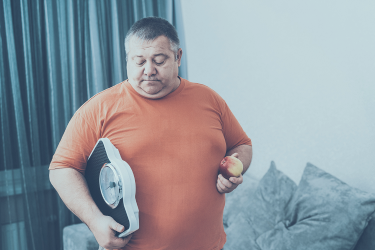 Obese man holding weighing scales and apple